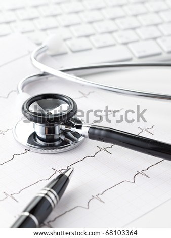 A stethoscope over a electrocardiogram close up. - stock photo