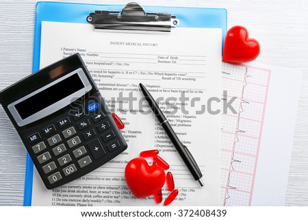 A stethoscope, pills, pen, calculator and clipboard, close-up - stock photo