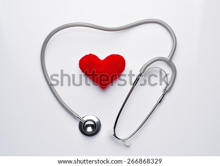 A stethoscope shaping a heart and a red heart over white background, view from above - stock photo