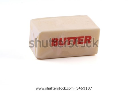 A stick of butter (1/2 cup) photographed from a slight angle above on white background. - stock photo