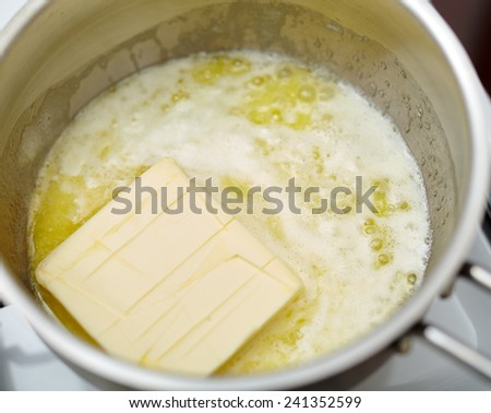 A stick of butter melting into a stainless steel pot on the stove - stock photo