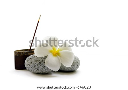 A stick of fragrant Japanese incense, some smooth pebbles and a frangipani flower - stock photo