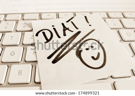 a sticky note is on the keyboard of a computer as a reminder: diet - stock photo
