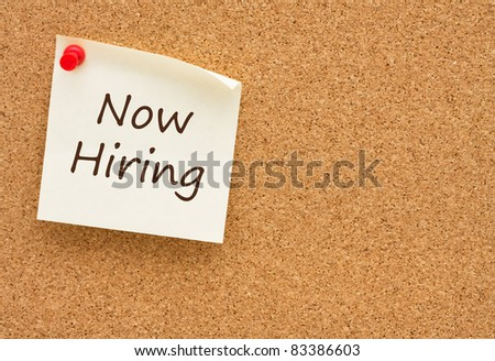 A sticky note on a cork board with the words now hiring on it - stock photo
