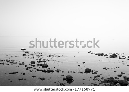 A still lake with the water blending into the sky, and rocks in the foreground.  Lake Huron, Mackinac Island, MI, USA. - stock photo