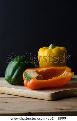 A still life arrangement of three bell peppers (green, yellow and orange) on a wooden chopping board, with planked kitchen table below and black background.  Moody lighting. - stock photo