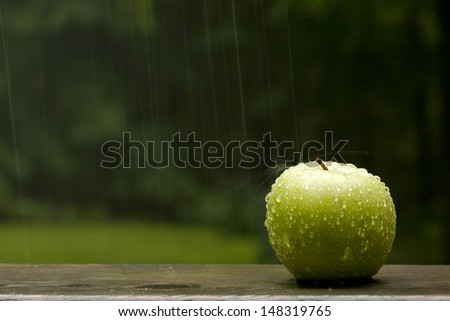 A still life of a green apple outdoors in the rain with droplets and splash on apple. - stock photo