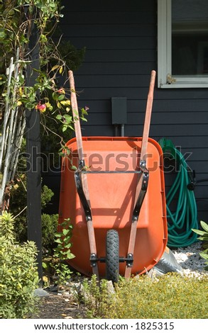 A still life of gardening tools, focusing on an orange wheel barrow leaning against a house, with a coiled green garden hose, and mulch.