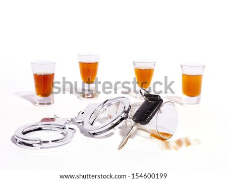 A still life of shot glasses, car keys and police handcuffs against a white background. - stock photo
