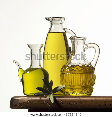 A still life of three bottles of olive oil on a wooden table - stock photo