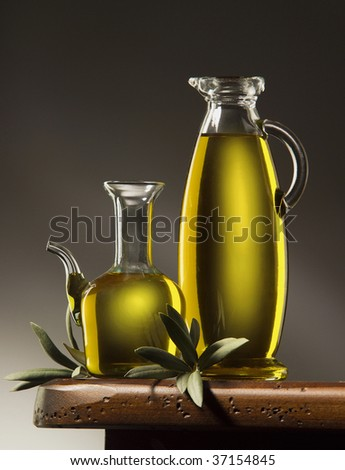 A still life of two bottles of olive oil wiyh leaves on a wooden table