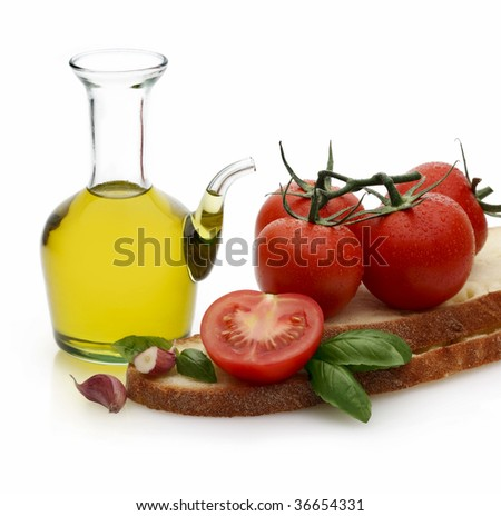 A Still life on white of tomatoes, oil, bread, garlic and basil