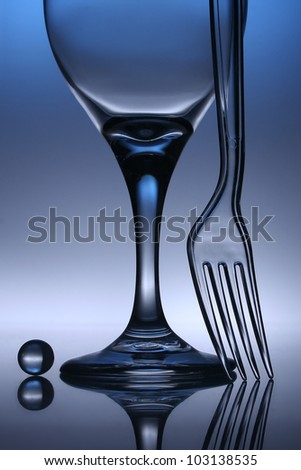 A still life photo with wine glass, fork and marble