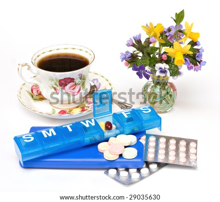 A still life scene with teacup, vase of spring flowers, assorted pills, drugs, vitamins, and dispensers. - stock photo