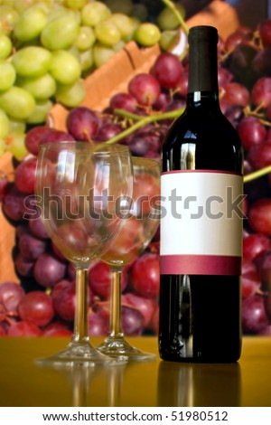 A still life shot of a single wine bottle and a pair of empty glasses in front of some red and green grapes.  Shallow depth of field. - stock photo