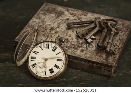 A still live of an arrangement of an antique pocket watch, skeleton keys and an old metal tin on a worn wooden table. - stock photo
