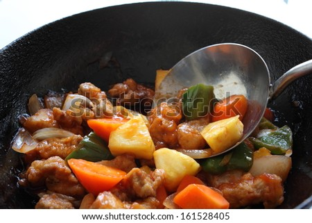 A stir fry of meat and vegetables cooking in a wok. - stock photo