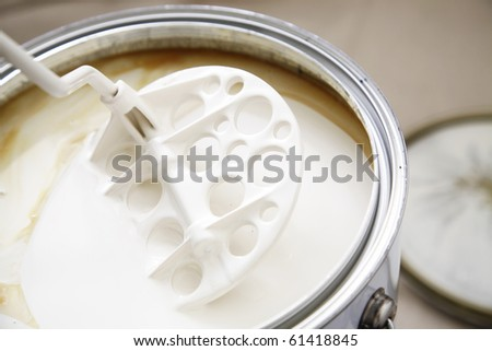 A stirrer used to mix the oil based warm white paint. - stock photo