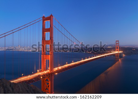 A stitched image of Golden Gate bridge that glows in the dusk (shot from Battery Spencer in Marin Headlands). Very rare colors - deep blue sky and water. Water is blurred because of long exposure. - stock photo