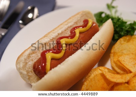A stock image of a hot dog on a bun, chips and parsley. Shallow depth of field.