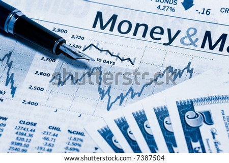 a stock market chart with a nice pen and some bills - stock photo