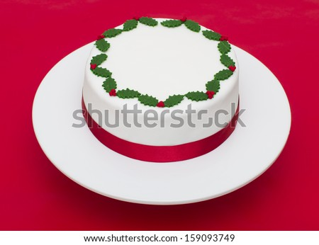 A stock photo of a Christmas cake on a red background - stock photo