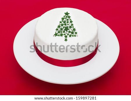 A stock photo of a Christmas cake with a Christmas tree decoration on a red background - stock photo