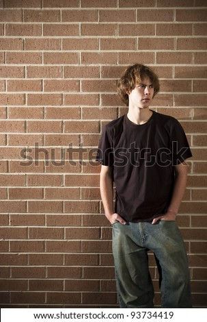 A stock photo of a young man  in casual clothes standing near a brick wall - stock photo