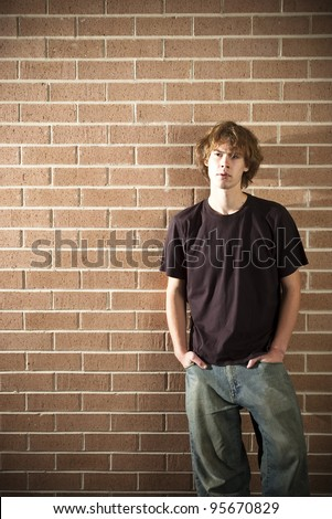 A stock photo of a young man standing near a wall in the afternoon light - stock photo
