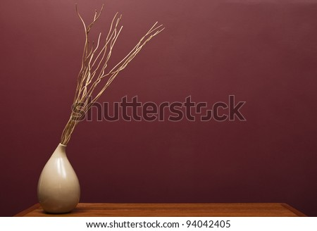 A stock photo with a vase with sticks on a table
