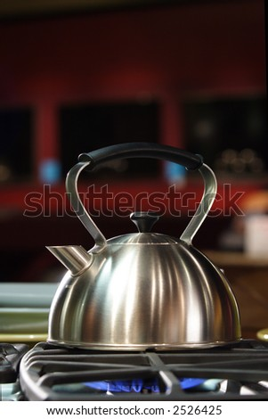 A stock photograph of a stainless steel tea kettle on a flaming gas stove. - stock photo