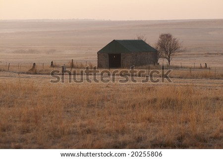 A stone barn stands in misty grasslands at dawn, Free State, South Africa. - stock photo