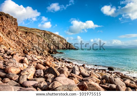 A stone beach with cliffs in background near dingle, Ireland. - stock photo