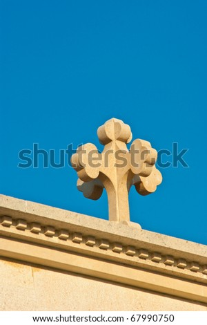 A stone cross on the side of a church - stock photo