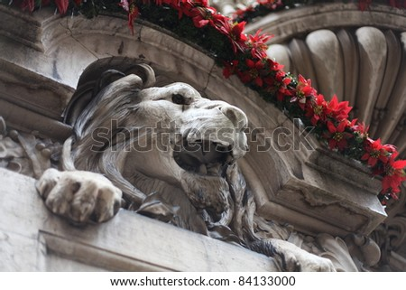 A stone lion during the Christmas season in Lisbon, Portugal. - stock photo