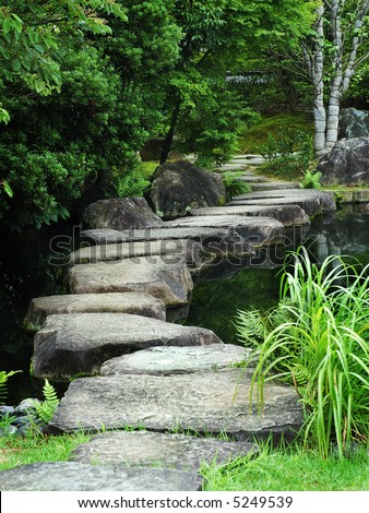 A stone path crossing a Koi pond next to Himeji-Jo Castle, Japan.