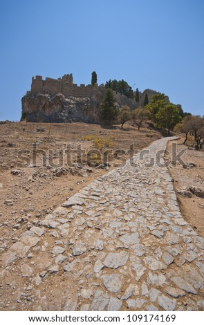 a stone path leading up to the acropolis at lindos on the greek island of rhodes. - stock photo