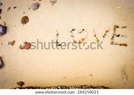 a stone placed love on sand background. - stock photo