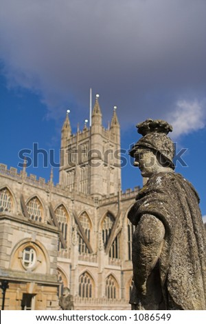 A stone Roman Soldier in the foreground of Bath Abbey in Bath, England. - stock photo