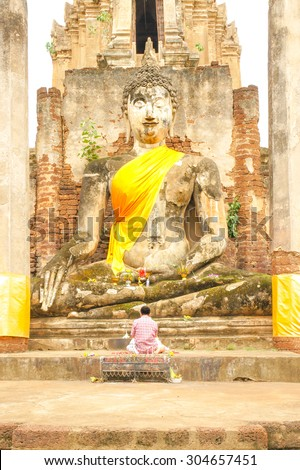 """A Stone Sculpture of Great Buddha [Sukhothai Style architecture], At """"Wat Mahathat"""" in Sukhothai Historical Park, Sukhothai Province, Thailand.  [Warm Tone Collection] - stock photo"""