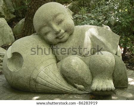 "A stone ""sleeping boy Buddha"" in the shades of a garden - stock photo"