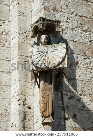 A stone statue of Angel holding sundial with the date 1528. Architectural detail of  the cathedral in Chartres (France). - stock photo