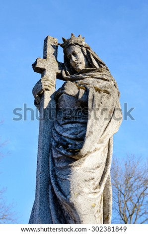 A stone statue of Jesus Christ on the grave in the old cemetery on the background of the sky - stock photo