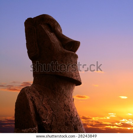 A stone statue on Easter island at sunset - stock photo