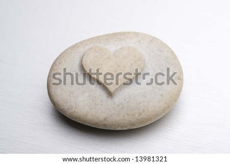 a stone with an engraved heart on a metal surface