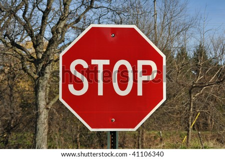 a stop sign against trees on an autumn day - stock photo