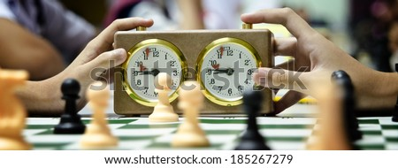 A stopwatch and a chessboard with a game in progress - stock photo