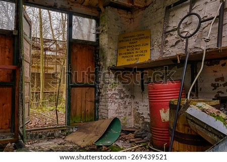 A storage room in an abandoned zoo. The sign says: 'No special feeding today because: the penguins are molting and in that period they have less appetite'. - stock photo