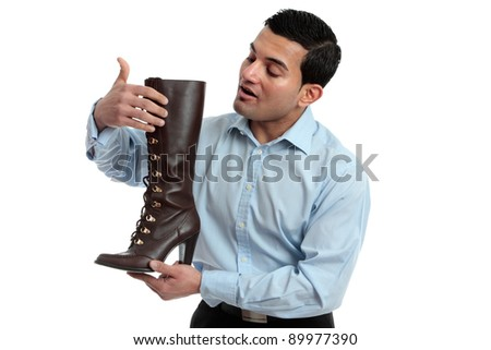 A store salesman showing a women's leather lace up boot.  White background. - stock photo