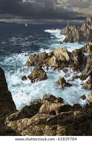 A storm tossed sea along a rocky coastline with sailboat. - stock photo